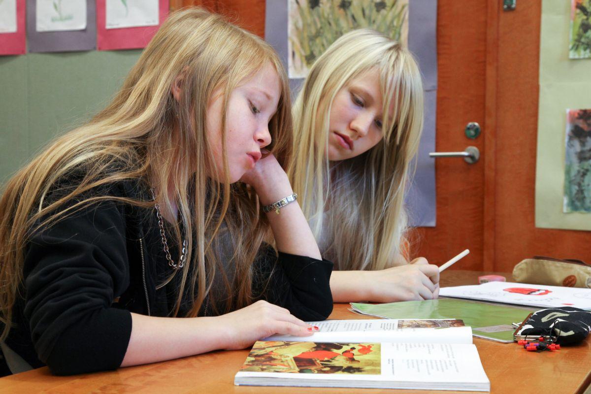 Kaksi tyttöä opiskelemassa koulun uskonnontunnilla